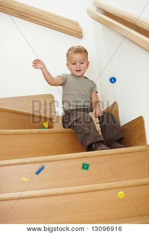 Happy little boy sitting on stairs, playing with colorful wooden toys.