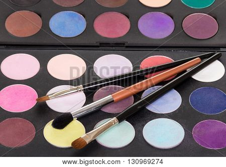 The palette of bright shadows and cosmetic brush make-up, background.