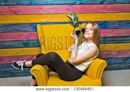 Fruit fashion girl sitting in a yellow chair. Young girl holds pineapple in sunglasses. Striped colorful background. Bright juicy picture