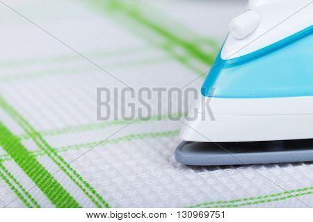 The front part of the steam iron, ironing cotton towel background.