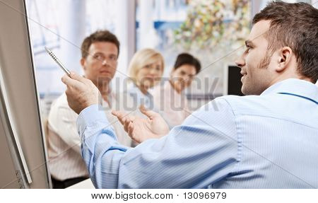 Young businessman speaking on business presentation in meeting room, pointing with pen, explaining, side view.