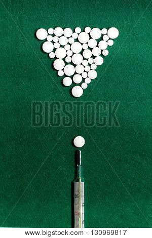 pool game with white pills and thermometer on green felt background flat lay concept
