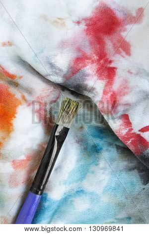 Paint brush on stained colorful cloth as a background