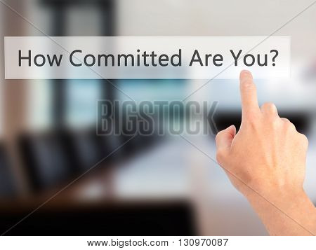 How Committed Are You - Hand Pressing A Button On Blurred Background Concept On Visual Screen.