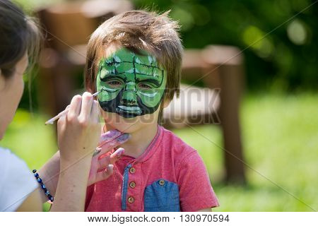 Cute Little Five Years Old Boy,. Having His Face Painted On His Birthday Party