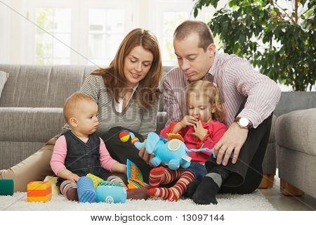 Glückliche Familie mit zwei Kindern spielen am Boden im Wohnzimmer zu Hause sitzen auf Boden vor