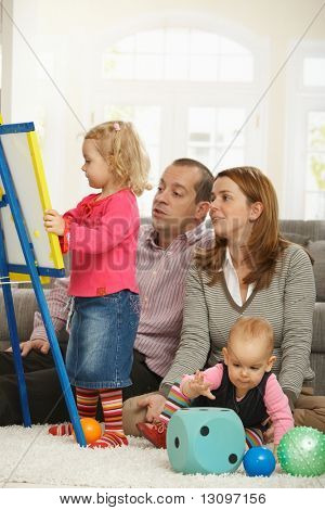 Parents watching toddler girl drawing on board, baby girl playing on floor.