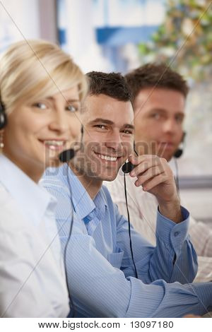 Happy young customer service operators talking on headset, eye contact, smiling.