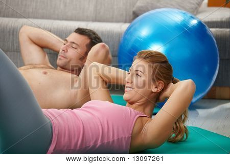 Young couple doing abdominal crunch lying on fitness mat at home in living room.