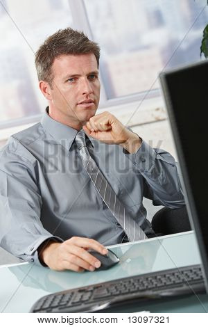 Determined businessman concentrating on computer task sitting in office.