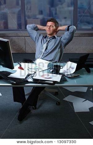 Tired businessman in office with papers lying all around, picture taken from high angle.