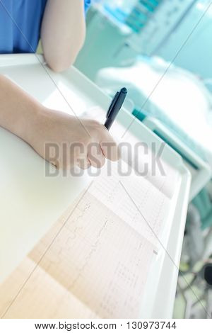 Doctor intently examines a cardiogram at the hospital.