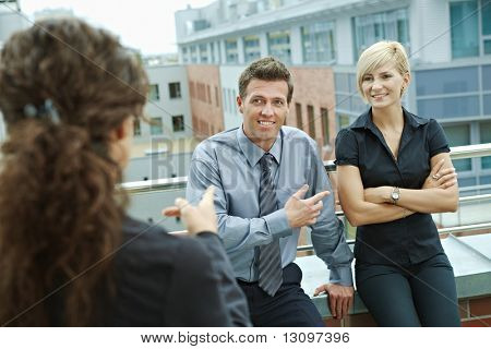 Business people talking on terrace of office building. Over the shoulder view.
