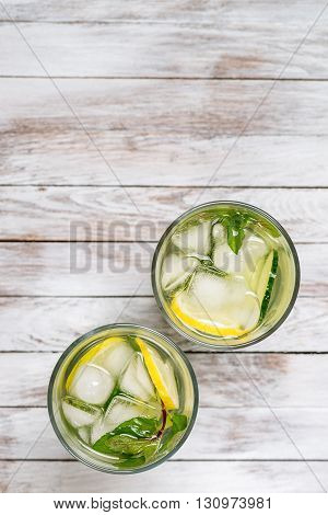 Water with lemon mint and cucumber on the wooden light background. Water Detox. Top view.