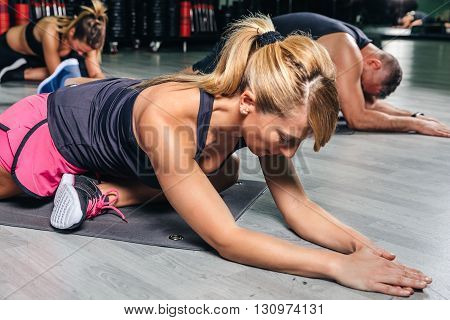 Close up of blonde woman stretching body in fitness class before training
