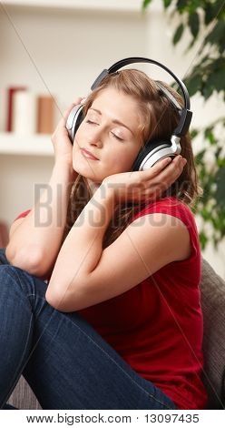 Teen girl listening to music on headphones with eyes closed smiling.