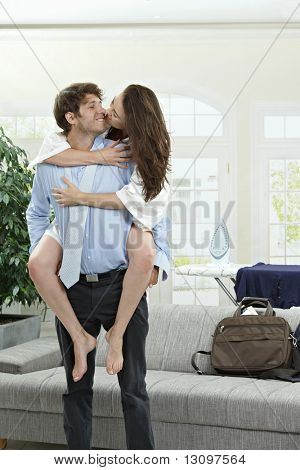 Happy young businessman holding his girfriend, kissing.