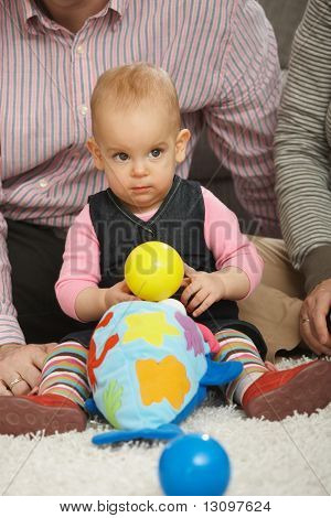 Baby girl sitting on floor holding ball playing with toys.