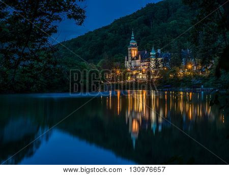 Lillafured palace at evening time. Illuminated building reflects in lake. Palace is surrounded with forest.