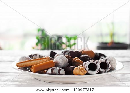 Sweet chocolate candies on white plate on white table in the room. Focus on foreground. Sweet plate from side view. Plate with chocolate candies and cookies.