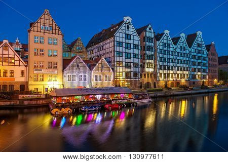 GDANSK, POLAND - MAY 05, 2016: Old historic granaries on the Granary Island with a restaurant on the water at night. Old Town in Gdansk is a tourist attraction for visitors.
