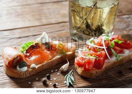 Salmon and tomato sandwiches on wooden table. Front view on almon and tomato bruschetta close up. Village style