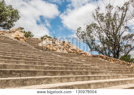 Rows of amphitheater seating, steps, boulders and trees at Mt. Helix Park in La Mesa, a city in San Diego, California.