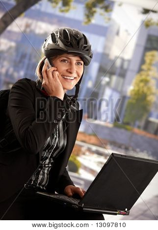 Portrait of young businesswoman wearing bike helmet, sitting in front of office building, using laptop computer.