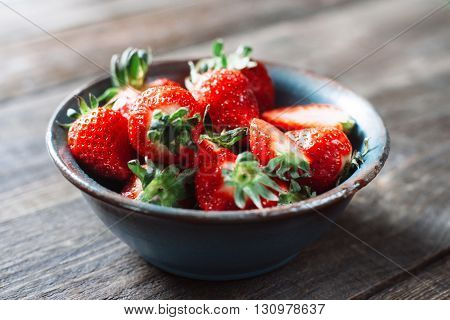 Bowl of fresh red strawberries on the wooden table. Close up. Fresh tasty mouth-watering red strawberries. Country style