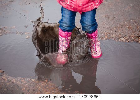Child wearing pink rain boots jumping into a puddle