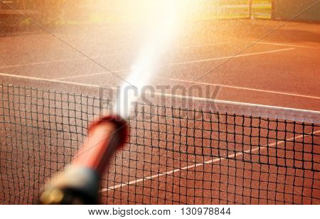 Maintenance sprinkler tennis court in sunlight