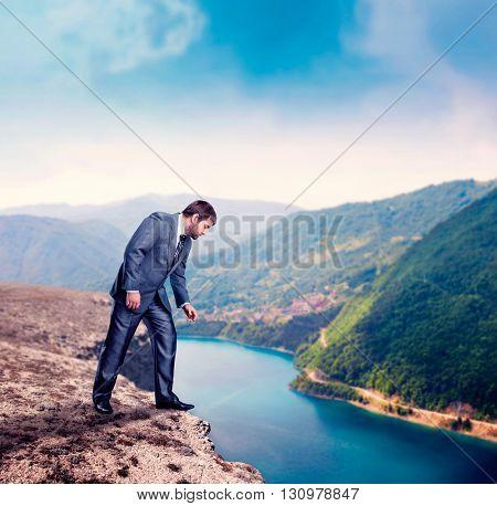 Businessman on the mountain edge