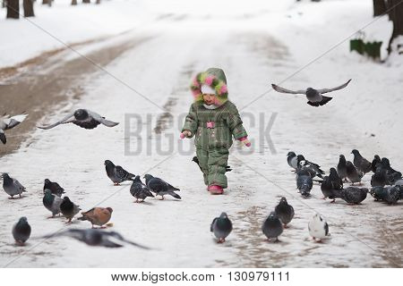 Child runs through a flock of pigeons on the square in winter city park