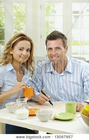 Couple drinking coffee at home, sitting at breakfast table, marking newspaper.