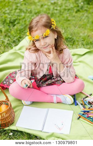 Sweet little girl drawing in the park on grass