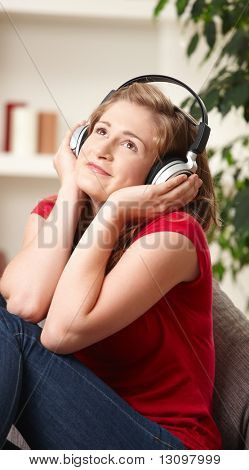 Happy teen girl listening to music on headphones sitting on couch at home smiling.