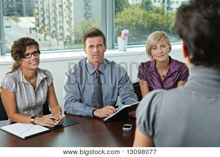 Panel of business people sitting at table in meeting room conducting job interview looking at applicant.
