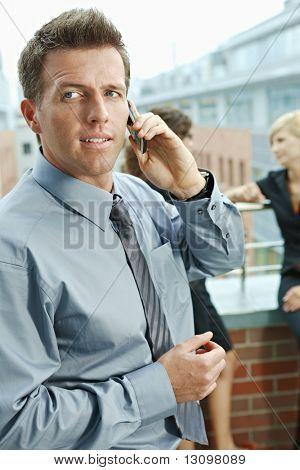 Empresarios hablando en la terraza al aire libre del edificio de oficinas. Empresario en frente con pho móvil