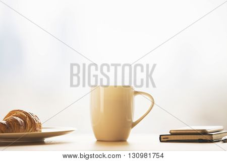 Closeup of tall coffee cup croissant on plate and notepad on top of phone