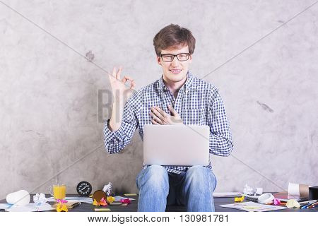 Smiling caucasian male with laptop sitting on messy desktop and showing ok sign