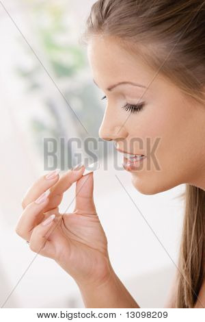 Beautiful girl taking chewing gum. Side view portrait.