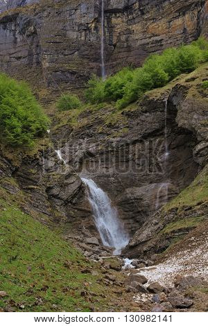 Spring scene in the Swiss Alps. Waterfall in Glarus Canton Kloental valley.