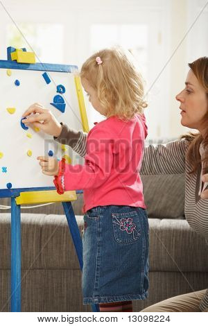 Little girl playing board game with mum in living room.