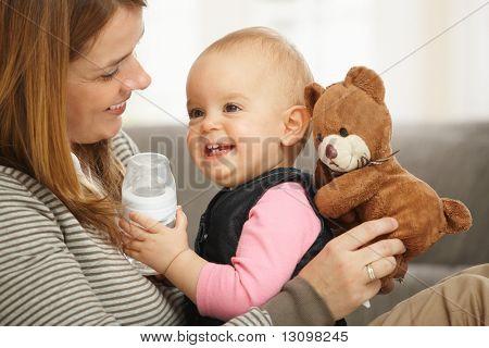 Glückliche Mama und Baby mädchen lachend Kuscheln halten Teddybär.