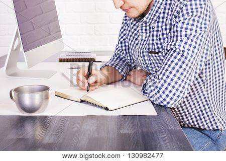 Businessman sitting at office desk with computer and iron mug and writing something in his diary