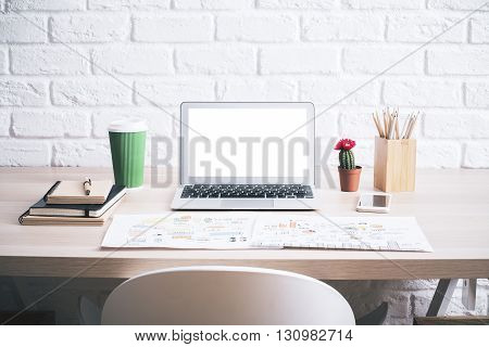 Creative hipster desktop with blank white laptop screen business sketch coffee cup cactus and other items on white brick wall background. Mock up