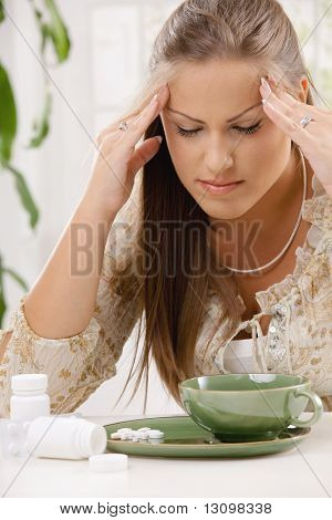 Young woman having headache, holding her head, leaning on table. Taking pills with tea.