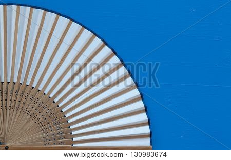 Typical Japanese hand fan made on the wooden blue table
