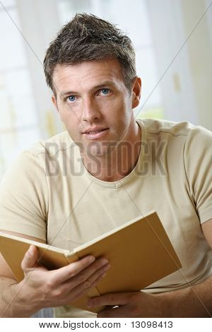 Mid-adult man at home sitting on couch with book handheld looking up at camera.