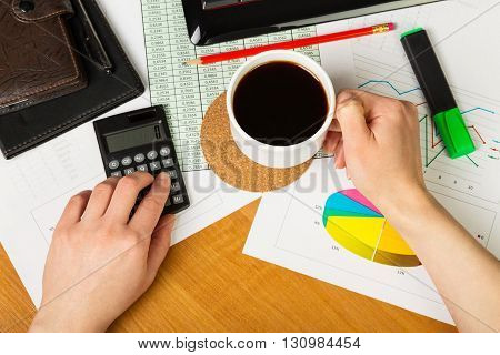 Calculator and cup of coffee in hand on the background of the desktop, view from above.